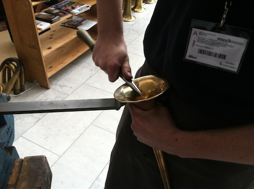 A German horn maker repairs a trumpet.