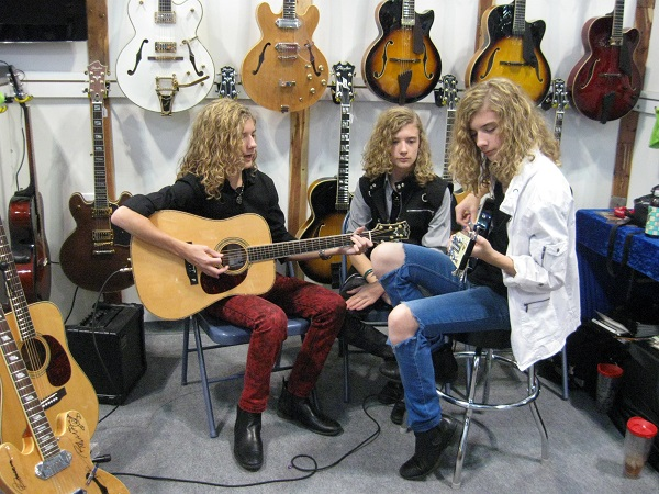 Chattanooga, Tennessee triplets Jared, Jordan and Justin Roberts check out some instruments from Utah's Peerless Guitars.