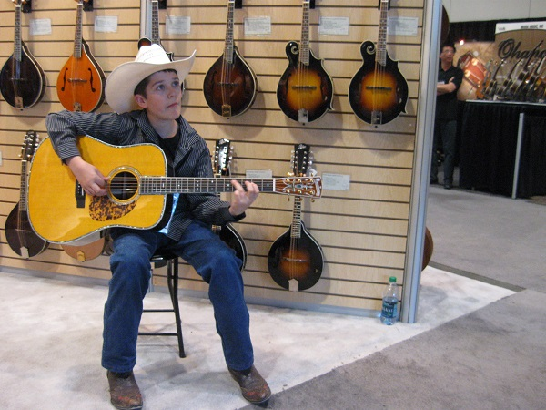"""Twelve-year-old """"Colonel"""" Isaac Moore of Camby, Indiana picks some bluegrass on a Blueridge guitar."""