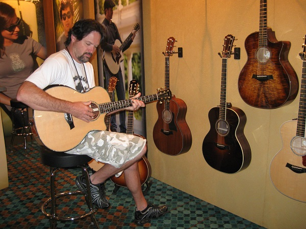 Patrick Murphy of Naples Park Music in Naples, Florida checks out an acoustic guitar in the Taylor room.
