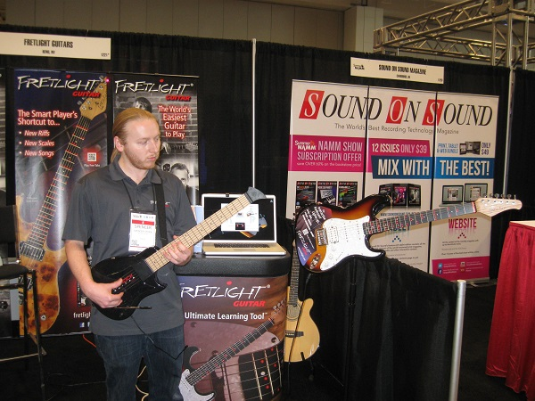 Spencer Stock demonstrates the Fretlight system, which uses a MIDI controller to make the frets light up on a special guitar to teach students where to put their fingers.